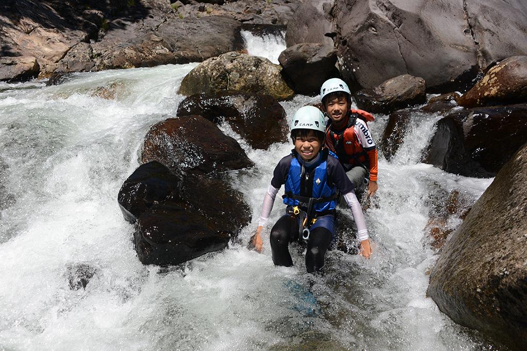 水しぶき舞う流れの中で、岩に腰掛ける兄弟の写真