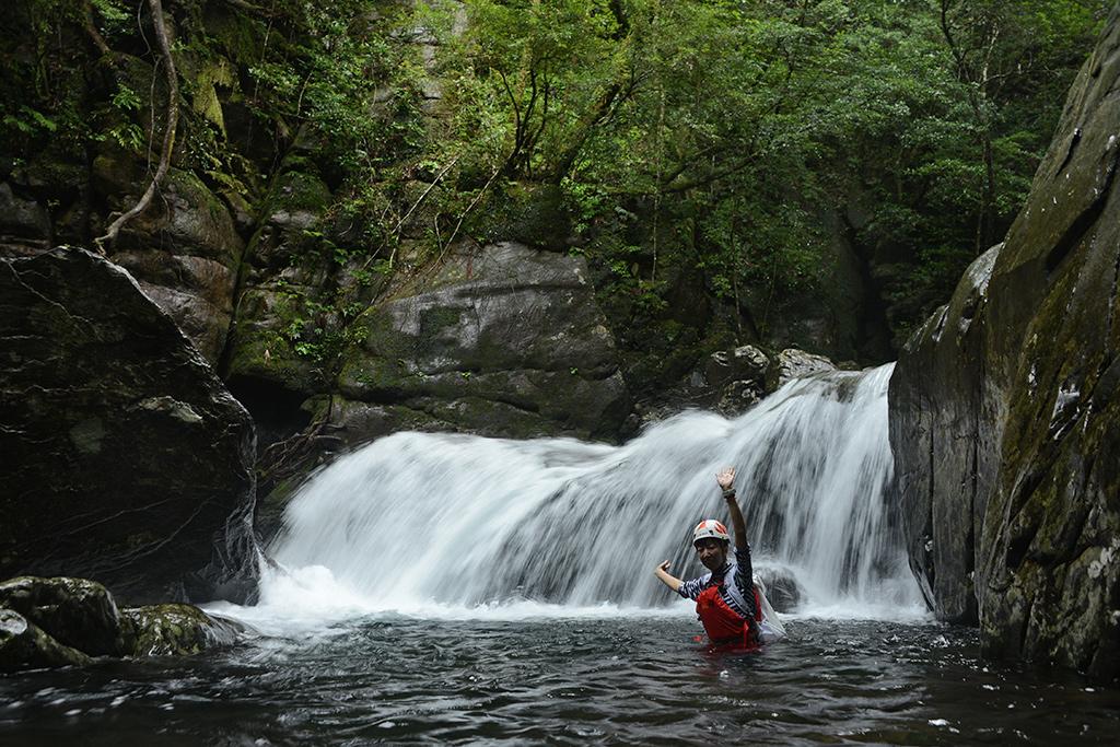 名物スポットの奥には滝があり、その滝を前に両手を広げてポーズをとるMさんの写真