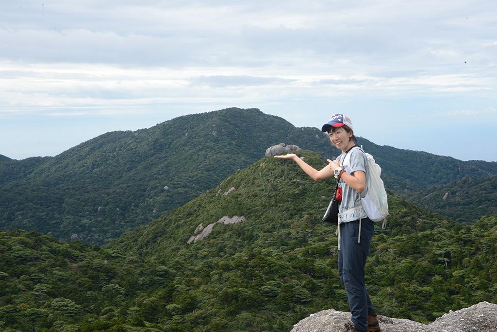 遠くに見える高盤岳にあるトーフ岩を手のひらに載せてみせるMさんの写真