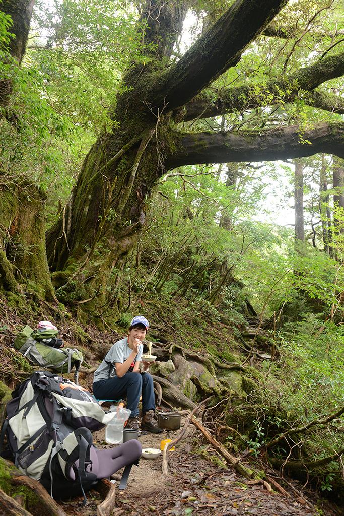森の中でラーメンを食べている満面の笑みを浮かべるMさんの写真