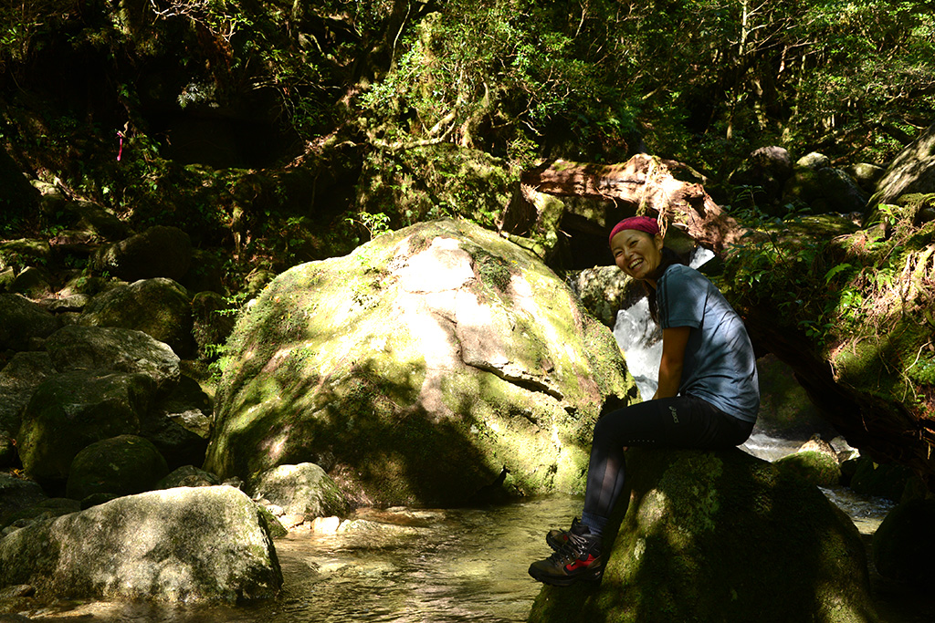 澄み渡る川の上の大きな石にまたがって、風景を眺める参加者の写真