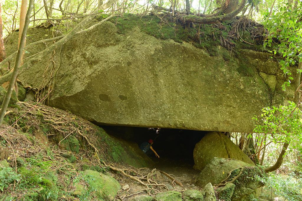 辻の岩屋という巨岩の下に入って見渡す参加者の写真