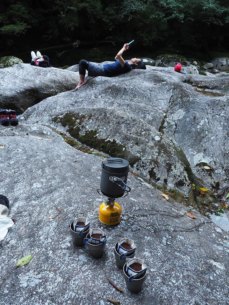 河原に寝転んでいる3人と、準備中のコーヒーたちの写真