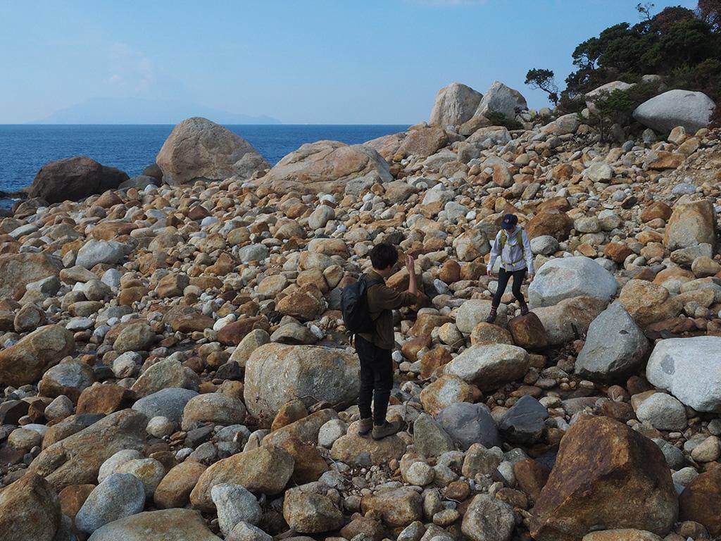 岩がゴロゴロと転がる海岸を歩く二人の写真
