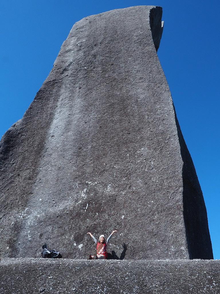 太忠岳山頂にある天忠石の前で大きく手を広げて歓びを表す参加者の写真