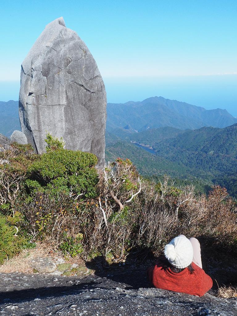 山頂から少し離れた場所から天忠石を眺める参加者の後ろ姿写真