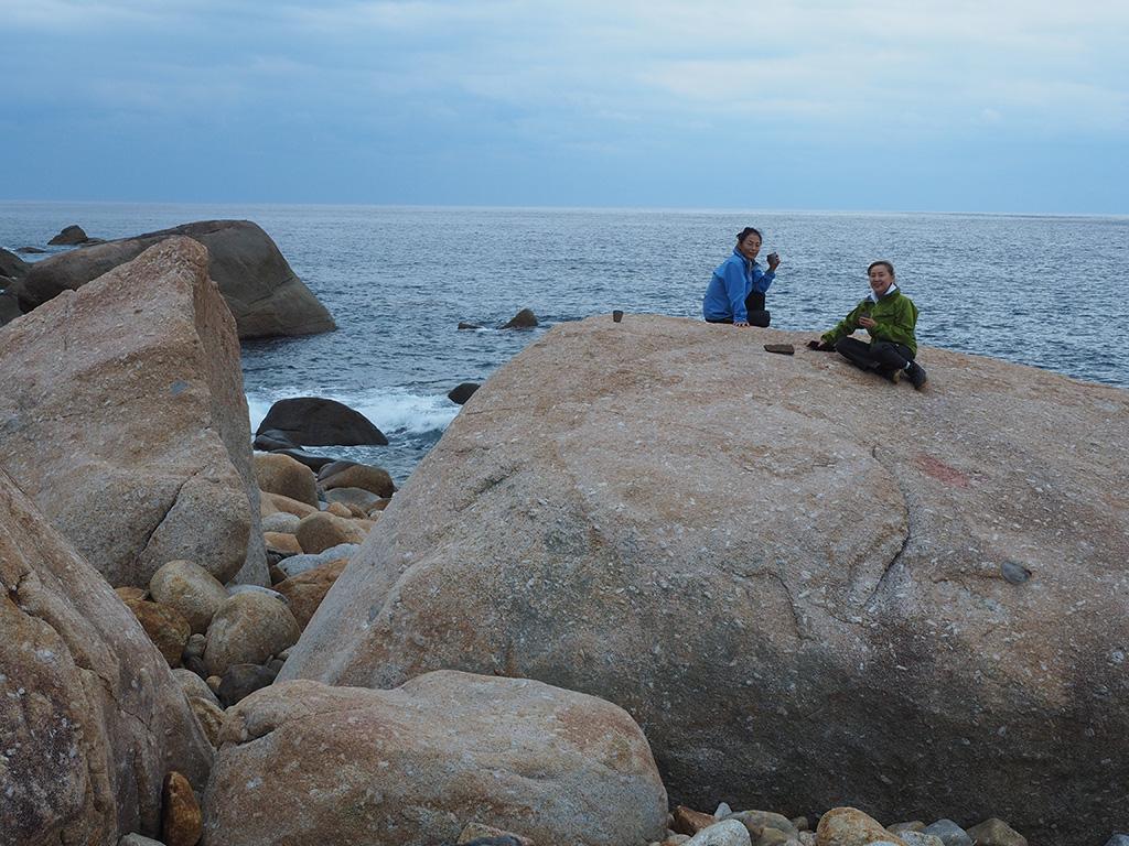 西部林道の海岸に転がる巨岩の上で、カフェタイムを楽しむ二人の写真