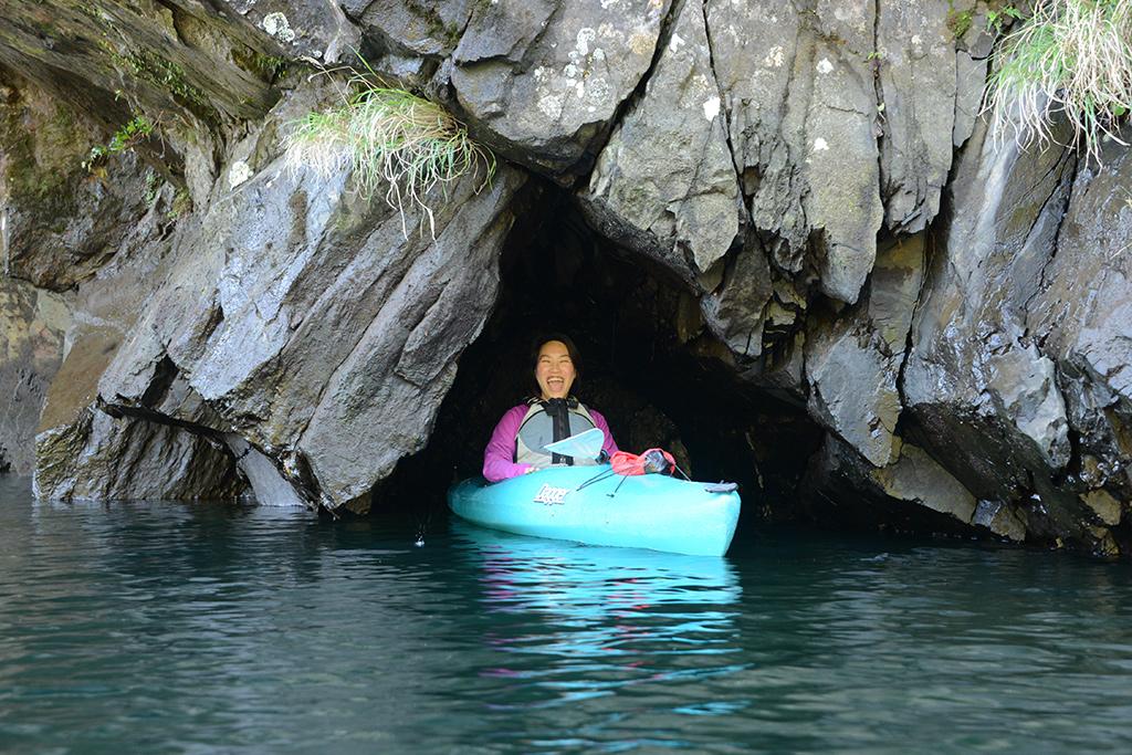 岩で出来た穴に、カヤックごと収まってみせるYさんの写真