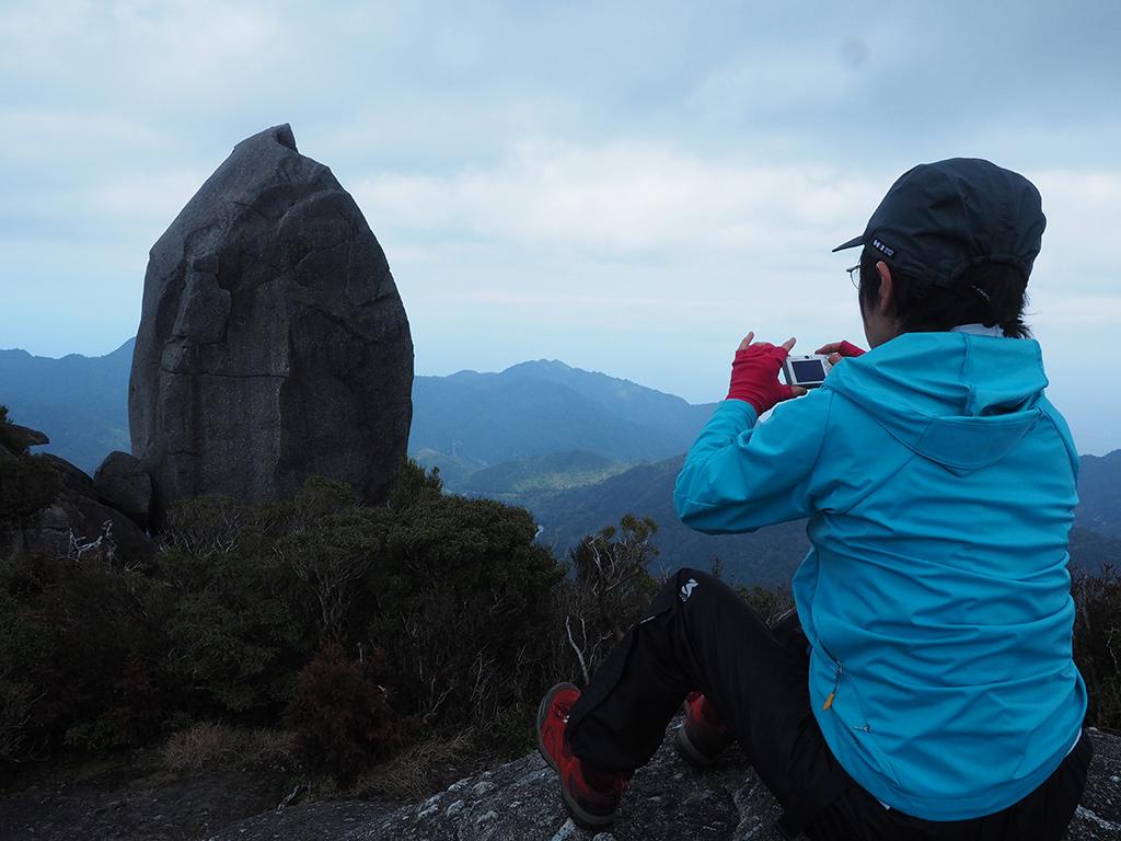 太忠岳山頂にある天忠石を眺める後ろ姿写真