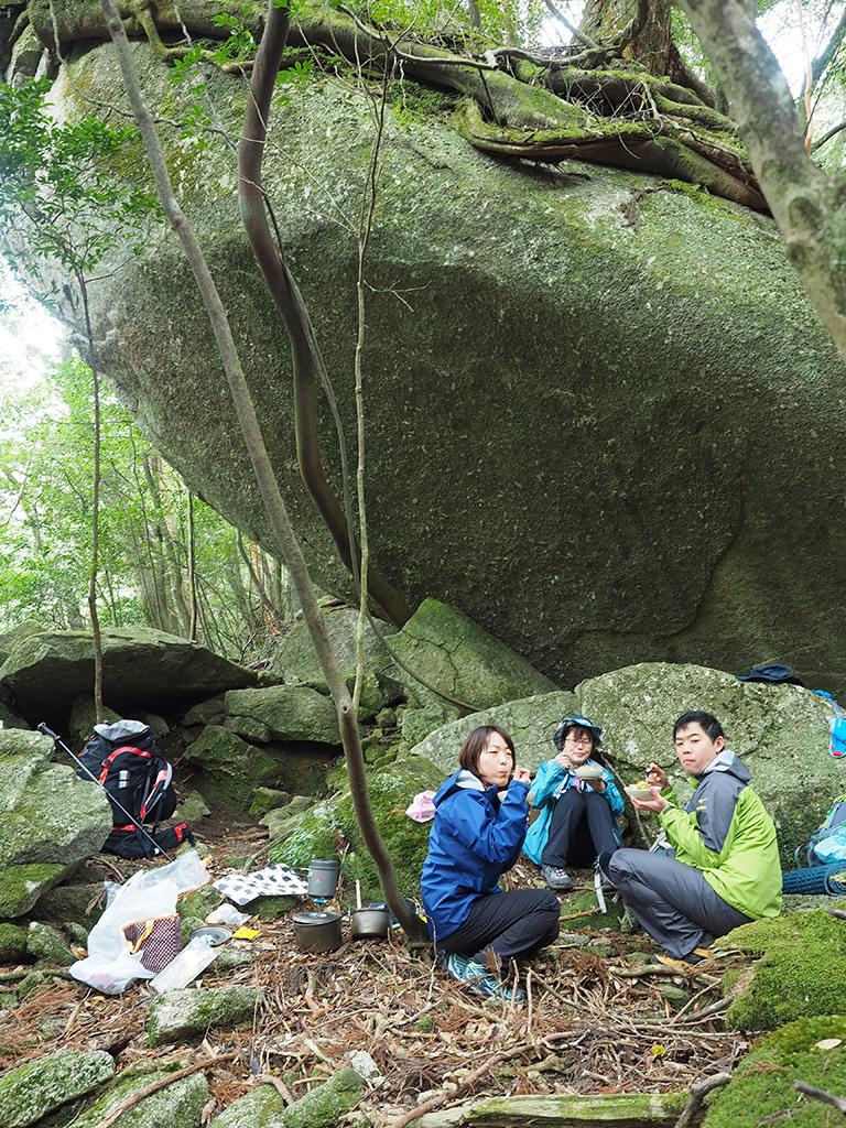 巨岩の下でご飯を食べる3人の写真