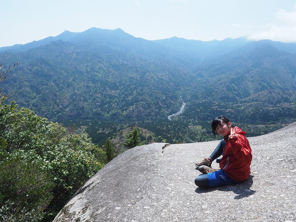 白谷雲水峡の最高地点・太鼓岩で強風を避けつつ笑顔を見せるNちゃん