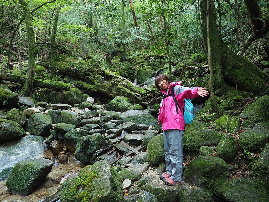 雨が落ちる森は苔が綺麗。緑の景色バックに両手を広げて感動を表すTさんの写真