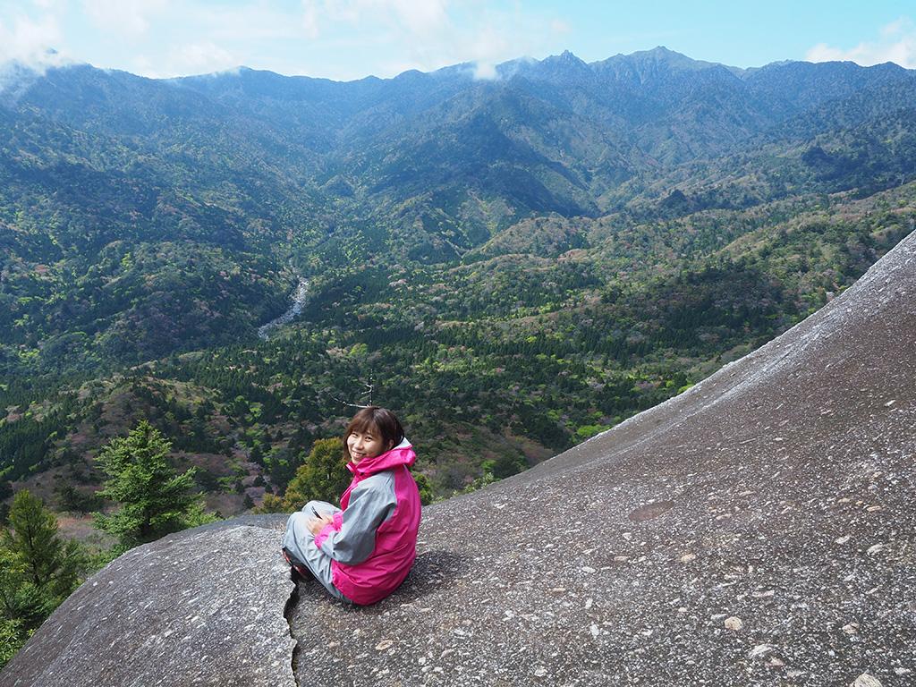 ヤマザクラが咲き誇る眼下の景色をバックに、座っているTさんの写真