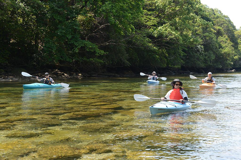 どこまでも透き通る水の上を滑るようにカヤックで漕いでくる家族の様子