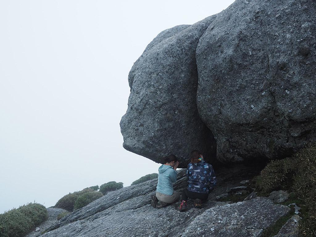 宮之浦岳山頂直下にある祠にお参りしている2人の写真