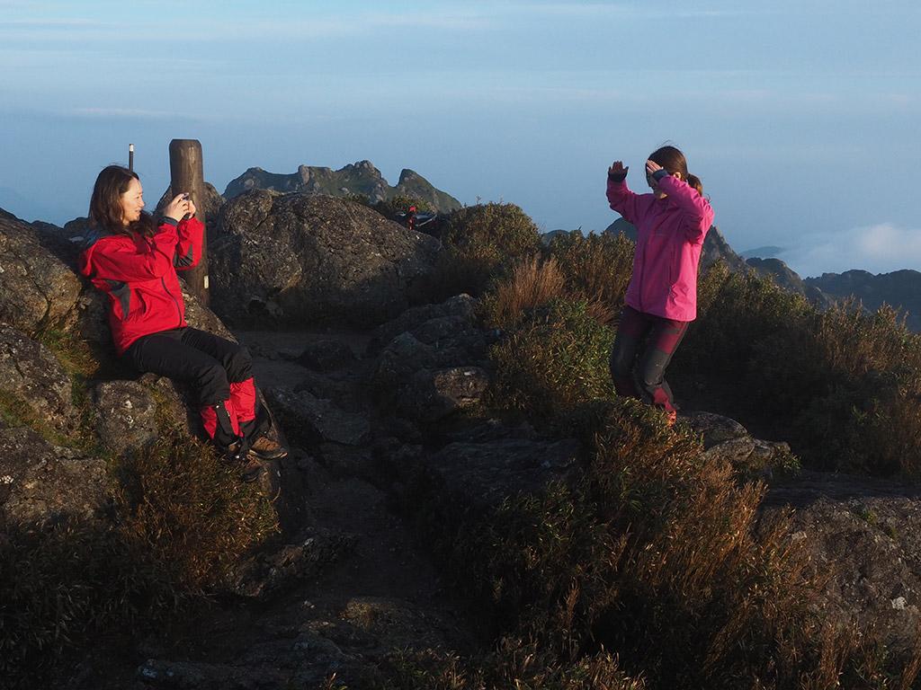 山頂のオリジナルポーズを求めて試行錯誤している二人の写真