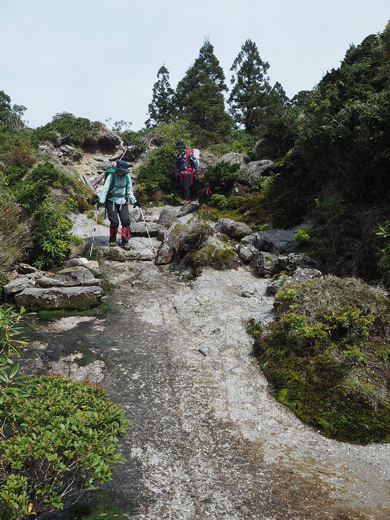 花崗岩が露出した急坂を下りる二人の写真