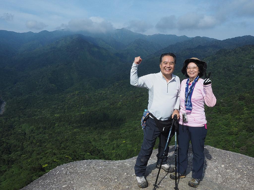 太鼓岩の上で絶景をバックにポーズをとるご夫婦の写真