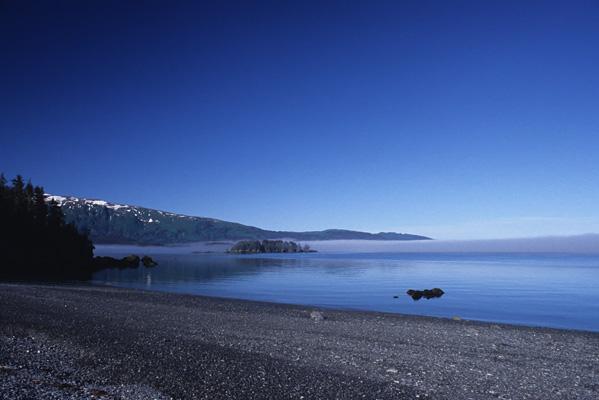 朝の水面に霧が立ちこめて、真っ青すぎる青空にアクセントを加えている風景写真