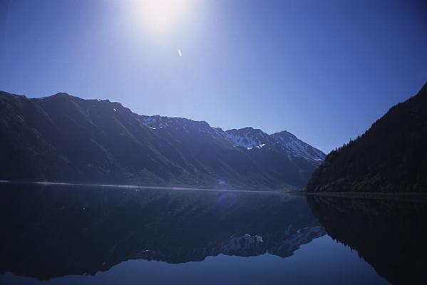 無風の水面が鏡のように両岸の山々を映しこんでいる写真