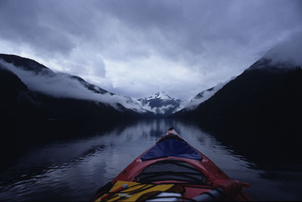 雪と雲に覆われる山々に囲まれ、鏡のような水面に漕ぎ出したカヤックと山の風景写真