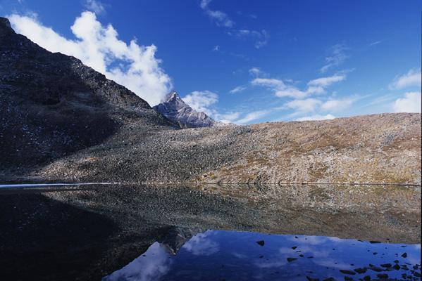 真っ青な空に、針のような山が飛び出し、その2つを静かな湖面が鏡のように映し出している写真