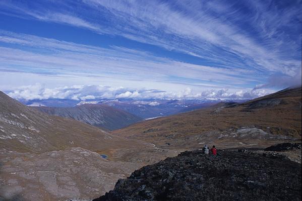 景色の見渡せる小高い場所で、2人座って遠くを眺めている遠景写真