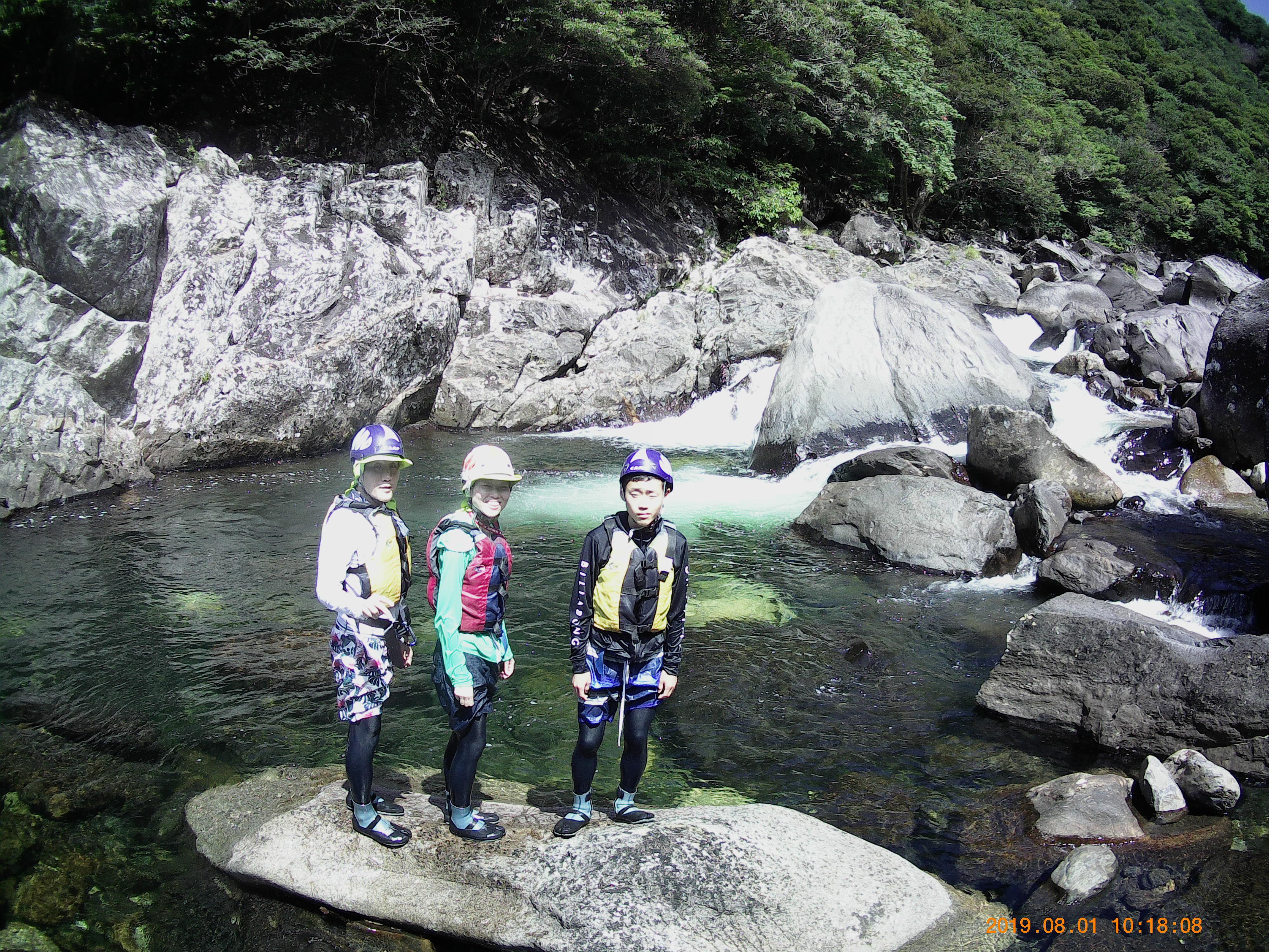 沢登りの途中で撮った家族写真(うしろの水が泡だってまるでメロンソーダのよう)