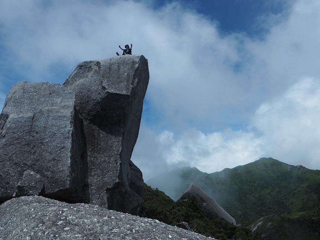 黒味岳山頂にある巨岩に座って両手を広げてポーズをとるUさんと風景写真