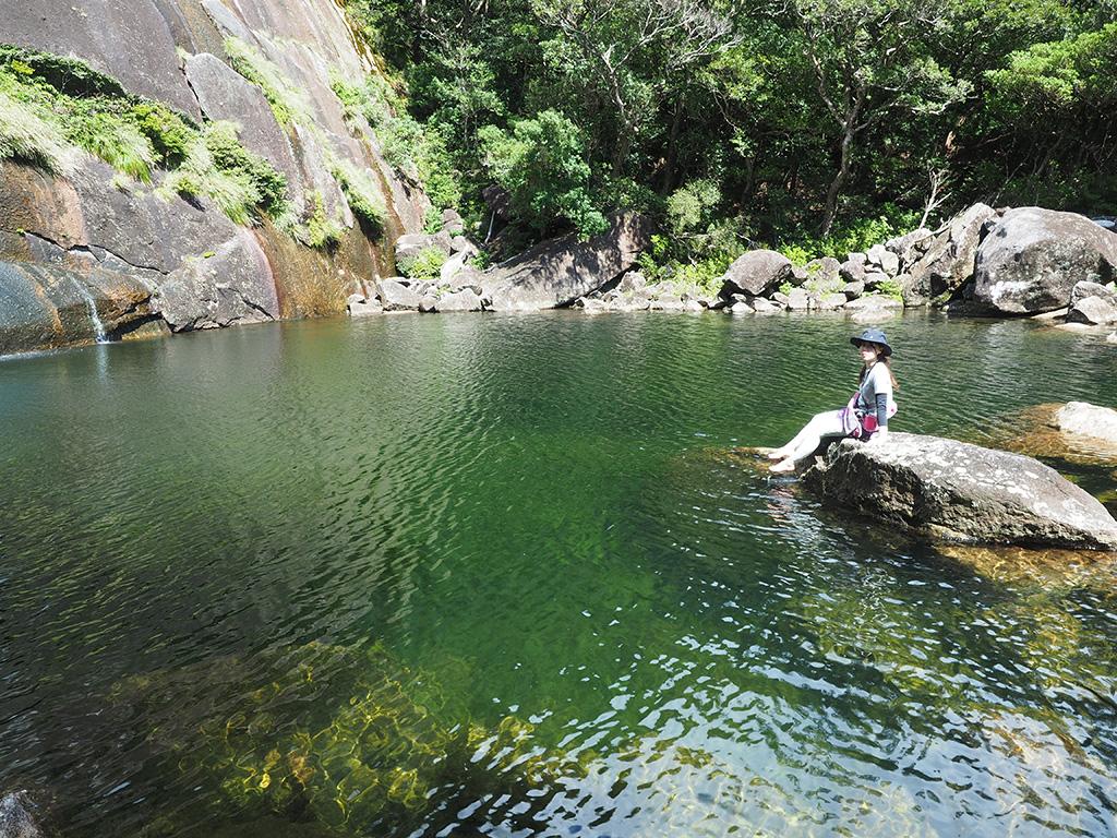 エメラルドグリーンに染まる蛇之口滝の滝壺に浮かぶ岩の上でのんびりと景色を眺めるMさんの写真