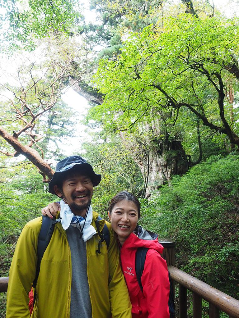 縄文杉をバックに弾けるような笑顔を見せるお二人の写真