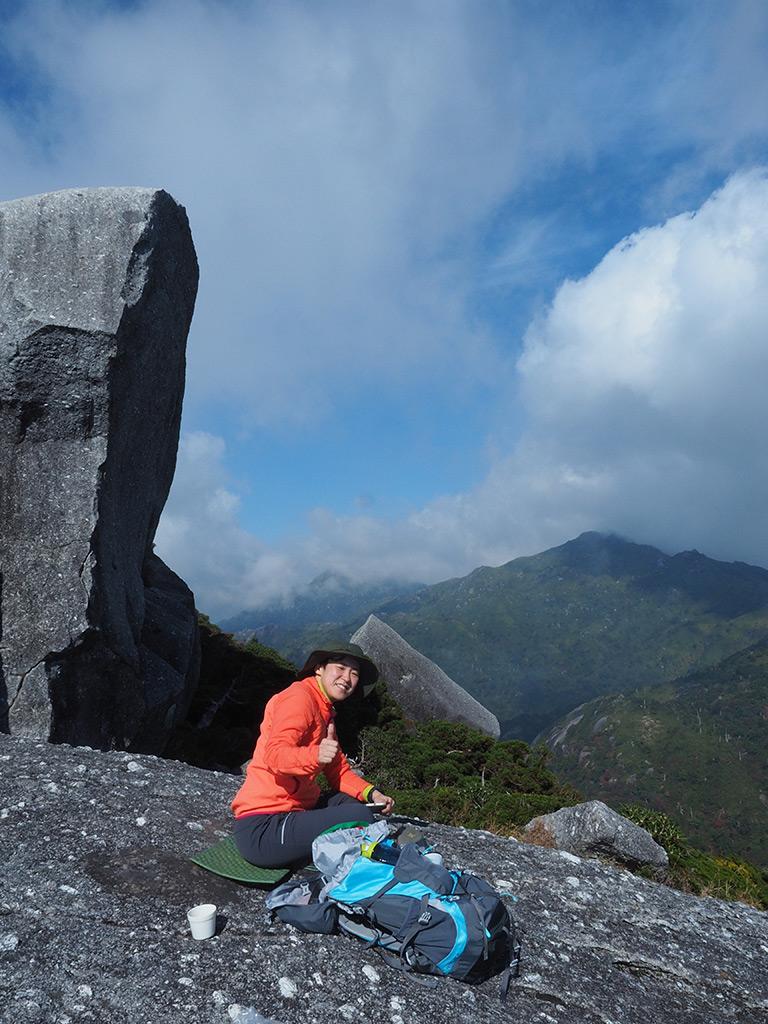 黒味岳山頂の巨岩と宮之浦岳をバックに撮ったTさんの写真