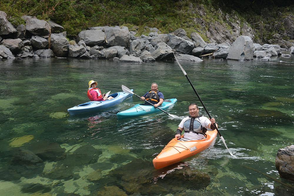 ご家族揃って、透明な安房川に浮くカヤック3艇