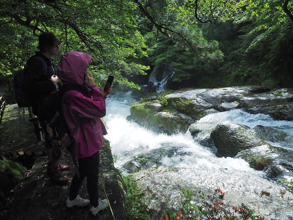 梅雨の雨で水量の増えた白谷川を覗く二人の写真