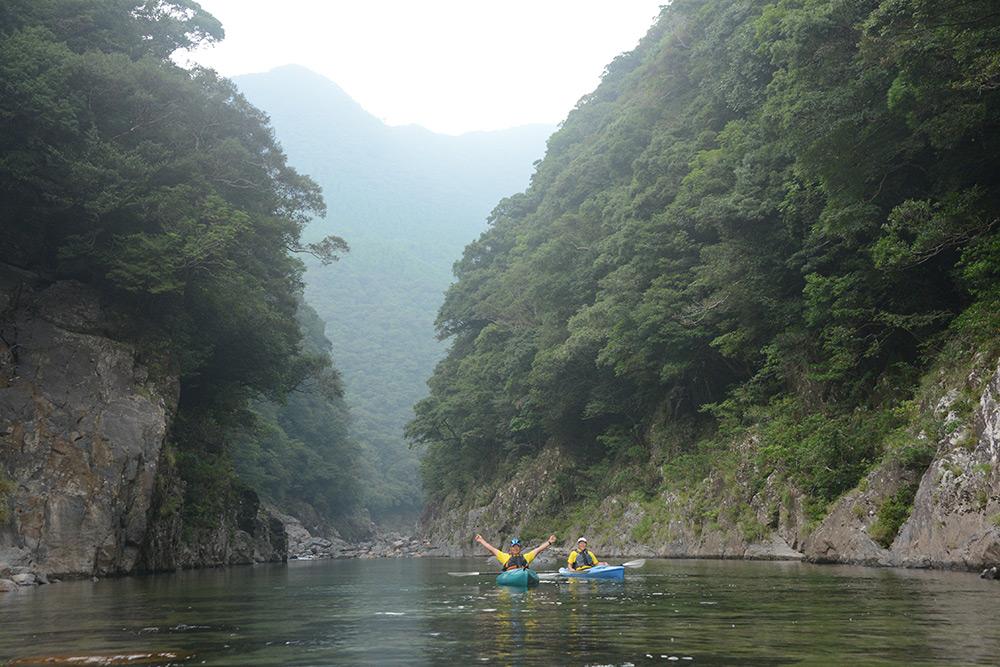 両側を急峻な山肌に囲まれた谷に浮かべたカヤック2艇とリピーターさんの写真