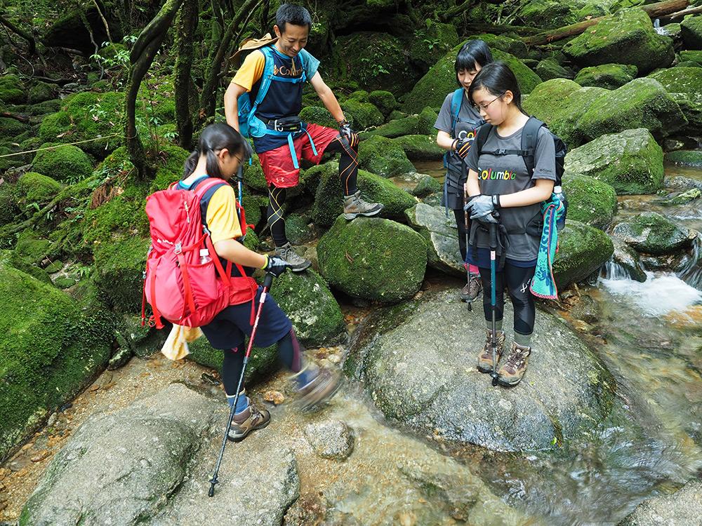 綺麗に水を登山靴でチャパチャパするKちゃんとそれを眺めるご家族3人の写真