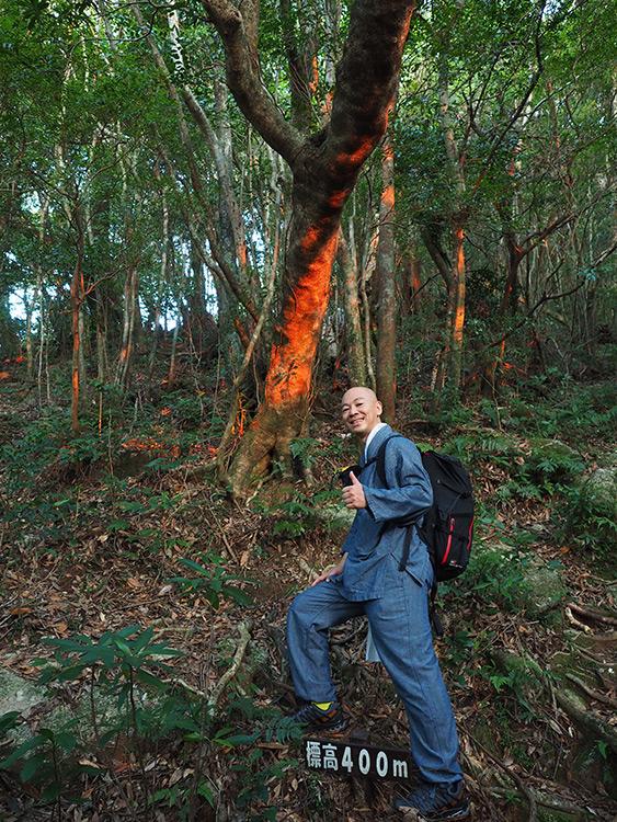 朝焼けを受けて朱く染まる木と参加者Kさんの写真