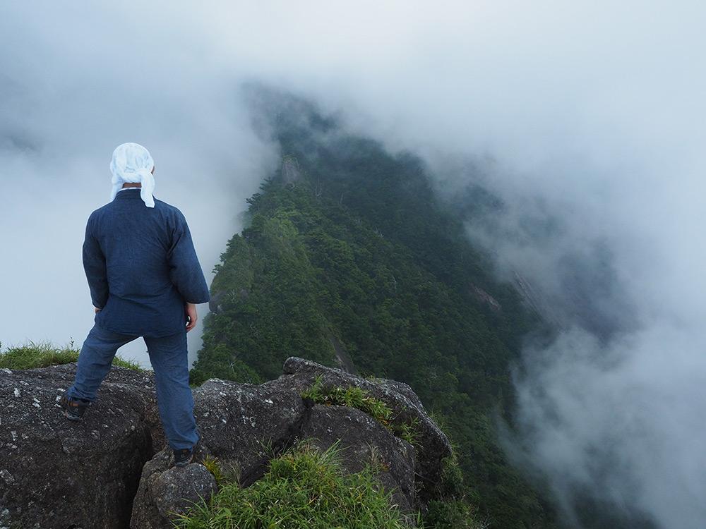 雲の切れ間から眼下の景色が顔を出し、その光景を眺めているKさんの後ろ姿写真