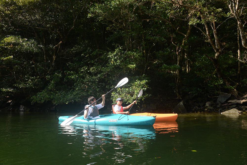 強い陽射しの中をカヤックで漕ぎ進む参加者2名の写真