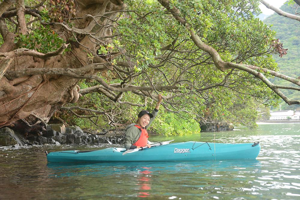 カヤックに乗りながらアコウの木に掴まってこちらを見る参加者Mさんの写真