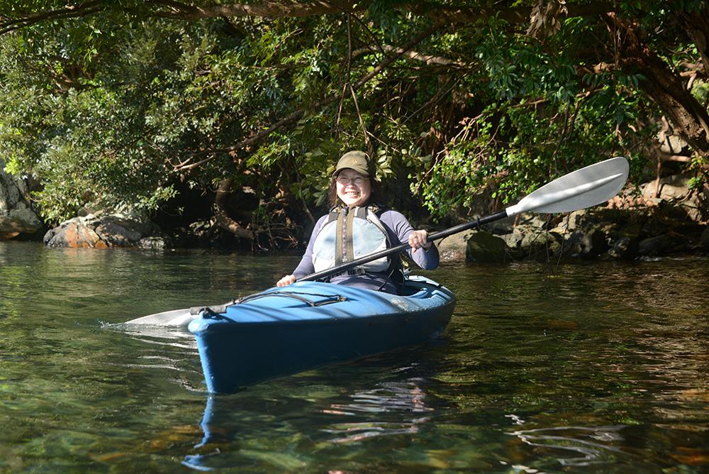 綺麗な水の上でノンビリすることを希望していたTさんが、水面に張り出した枝の下でカヤックに乗っている写真