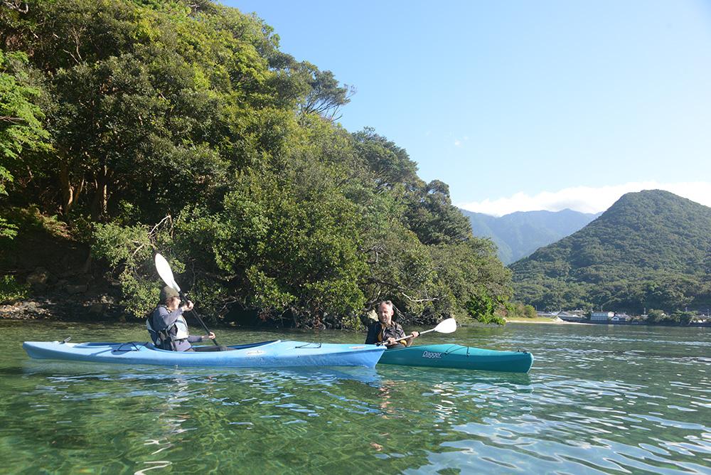 美しい水面に浮かび、岸沿いでカヤックを押し合っている二人