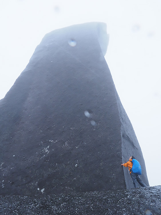 天忠石を伝う雨粒が風にさらわれていく様を楽しそうに見上げているSさんの写真