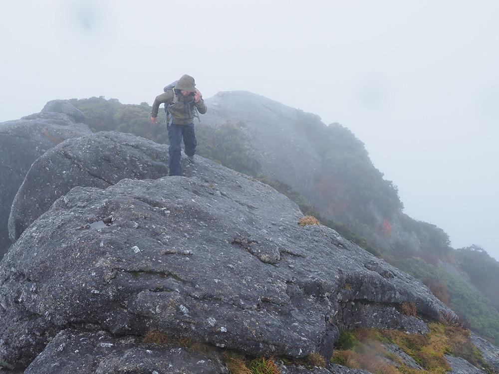 時折爆風が吹く中、亀裂の入った岩をジャンプして飛び越えたTさん