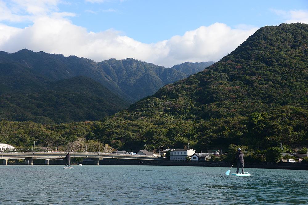 山々が連なる様子さえ見ることができた晴れの栗生川にSUPで浮かぶ二人の写真