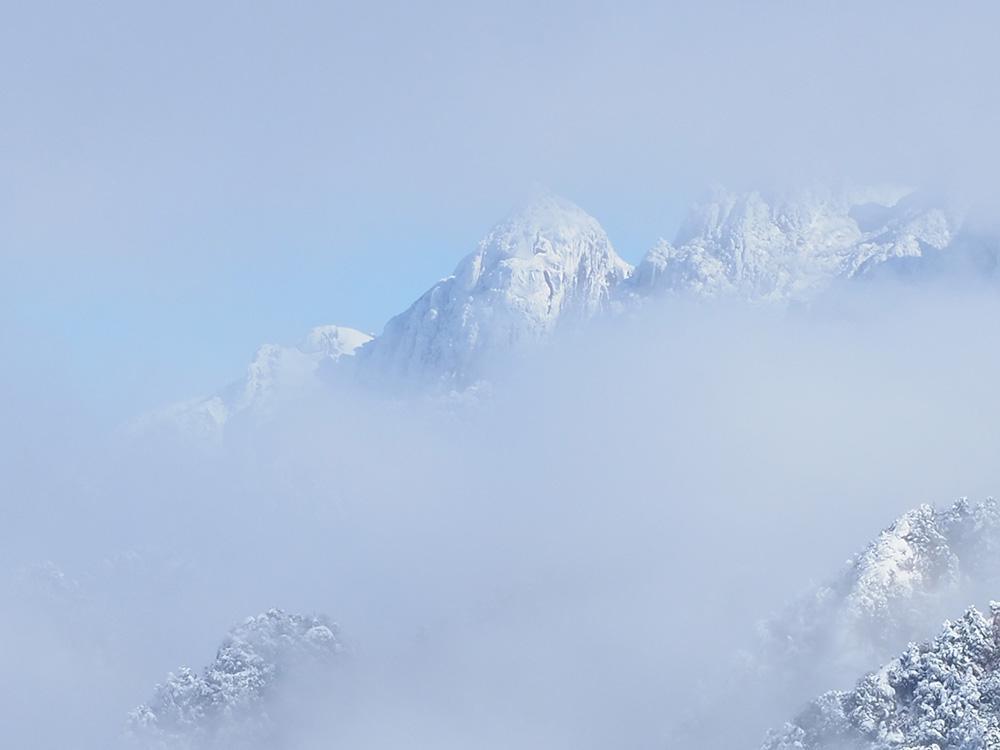 雲の合間から顔を覗かせた真っ白に冠雪した永田岳の写真