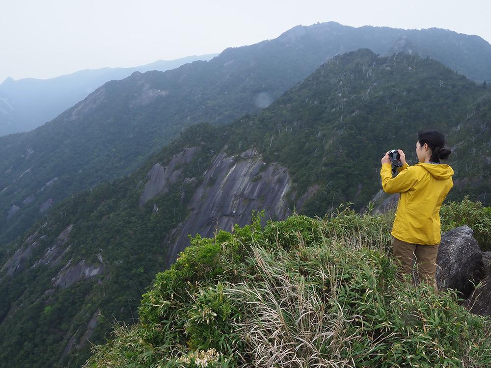 花崗岩の岩壁に感動するMさんが写真を撮っている写真
