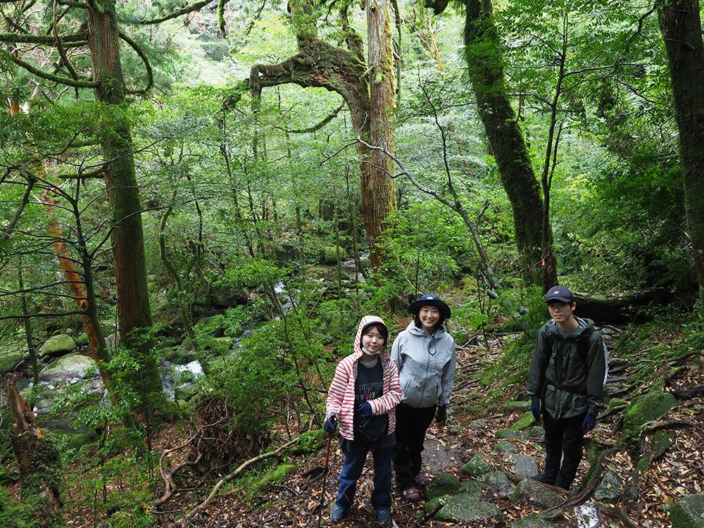 背景にスギと沢がある風景に立つ3人の写真