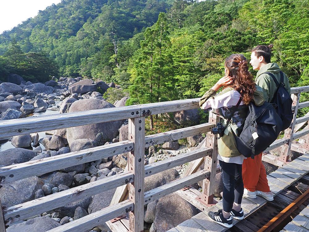 小杉谷橋の上で、河原に並ぶ巨岩を眺める二人の写真