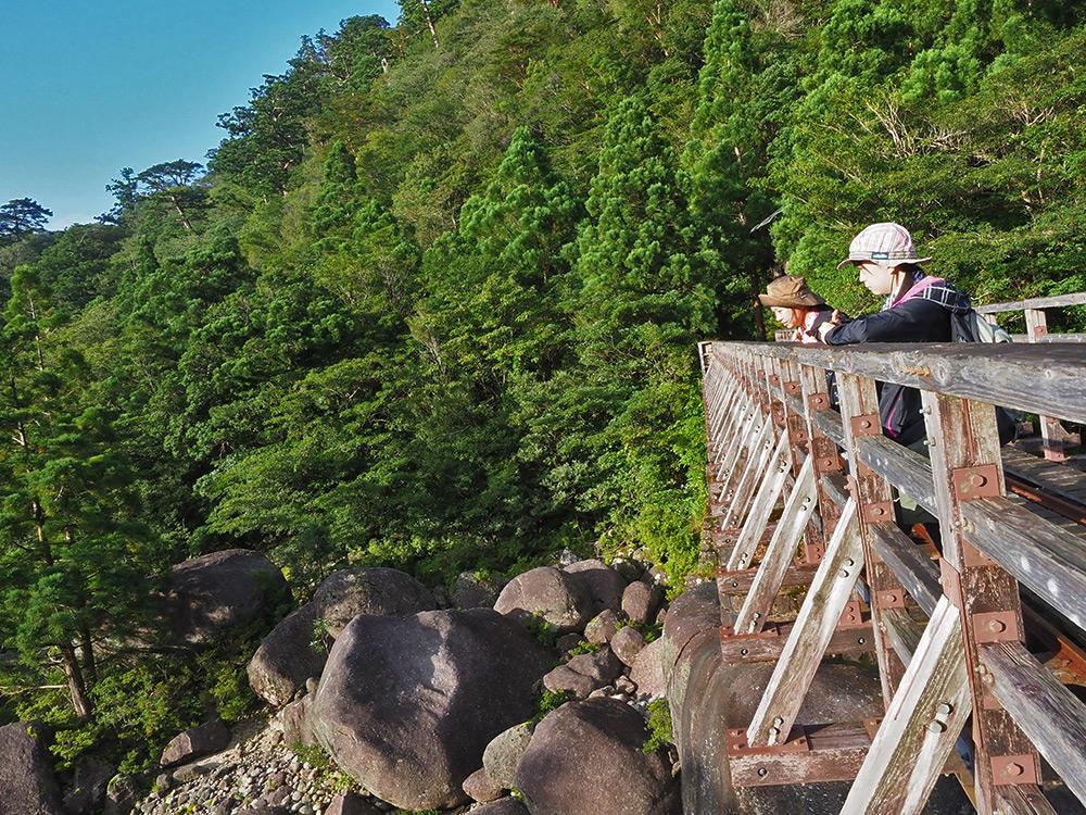 橋の手すりに寄りかかり朝の景色を眺める二人の写真